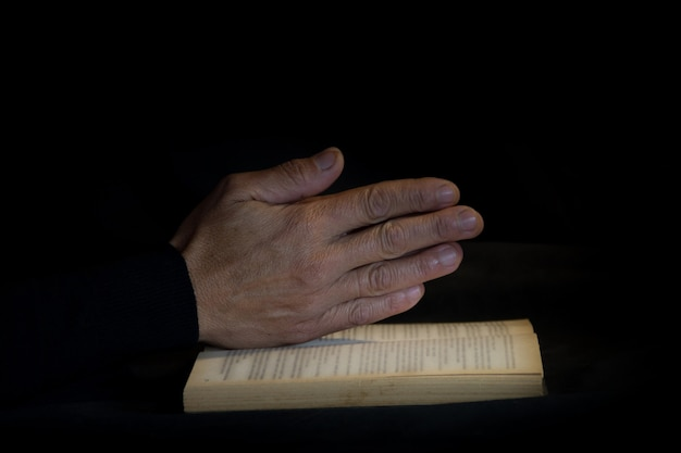 Praying hands on black background. faith and praise concept