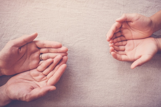 Praying hands of child and adult, compassion donation, charity, helping hands concept