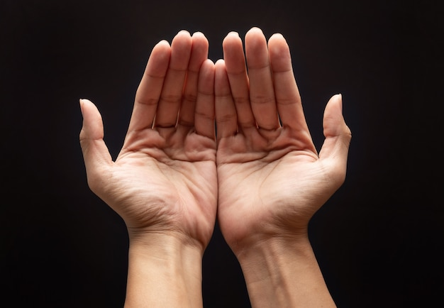 Praying hands in the dark wall with faith in religion and belief in god.