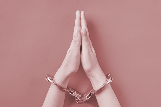 Praying hands in handcuffs. life imprisonment concept. deprivation of liberty and arrest perpetrators.
