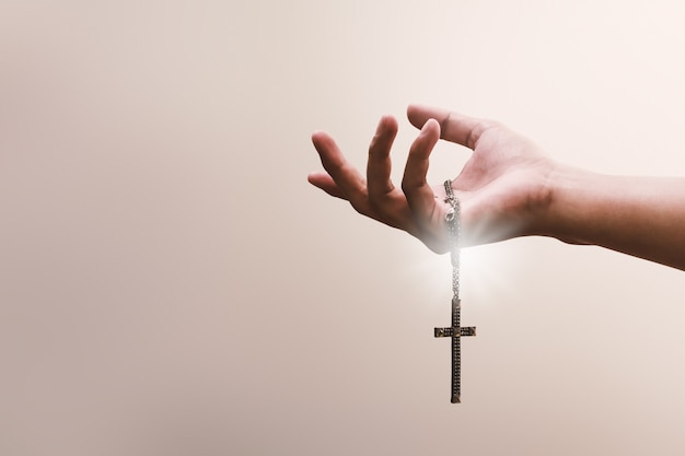 Praying hands hold a crucifix or cross of metal necklace with faith in religion and belief in god