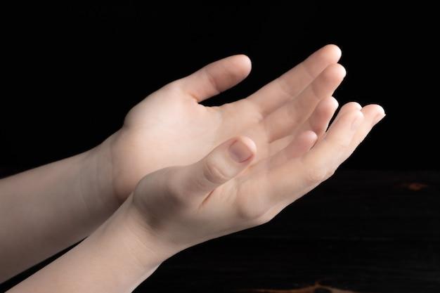 기도하는 손은 손에 빛이 있는 어둠 속에 있습니다.