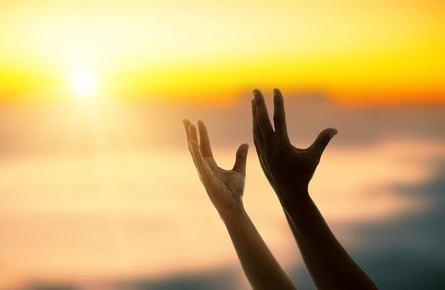 일몰에 그의 신을 축복하기 위해 한 남자의 손에 기도. 모든 종교의 사람들, 기독교인, 이슬람교도, 불교도는 믿는 신을 겸손하게 하고 삶에 대한 희망은 세계 평화, 태양 광선 배경을 사랑합니다