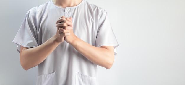 흰색 배경에 고립 된 흰색 캐주얼 헝겊을 입고 아시아 남자의 손을기도