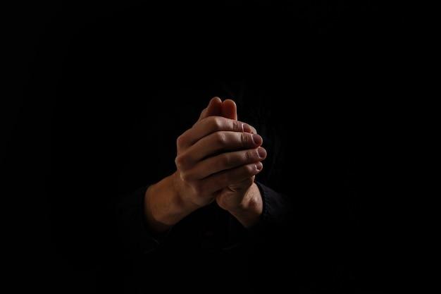 검은 배경에 기도하는 손