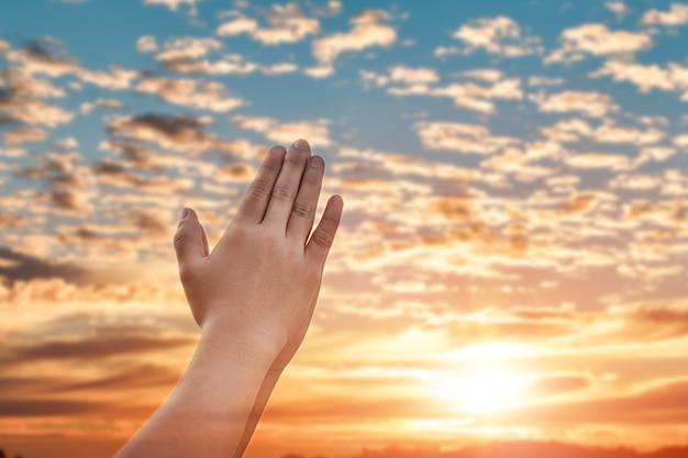 흐릿한 일몰 하늘 배경 위에 종교에 대한 믿음과 신에 대한 믿음으로 손을 기도합니다.