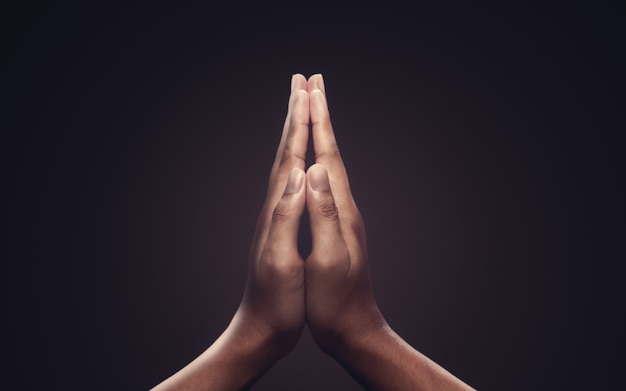 Praying hands with faith in religion and belief in god on dark background