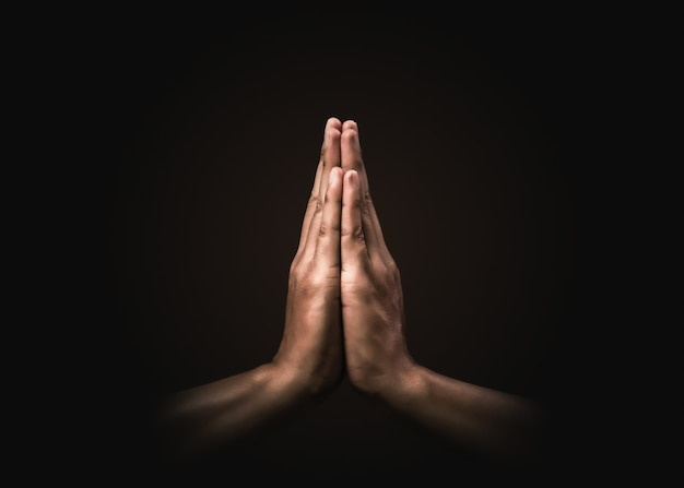 Praying hands with faith in religion and belief in god on dark . power of hope or love and devotion. namaste or namaskar hands gesture. prayer position.
