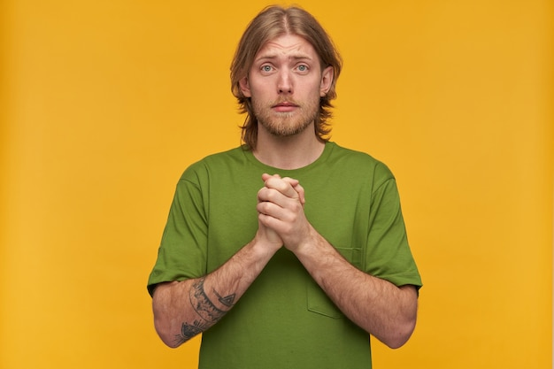 Praying male, begging bearded guy with blond hairstyle. wearing green t-shirt. has tattoos. holds palms together and plead.  isolated over yellow wall
