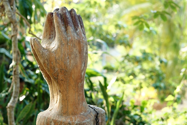 Praying wooden hands on green nature background