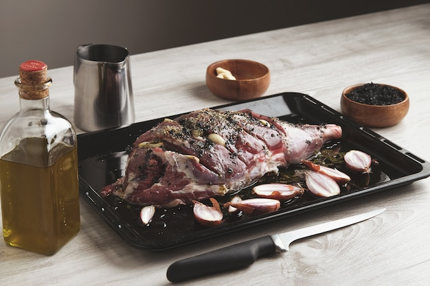 Pre cooked icelandic lamb leg meat wit spices and herbs and small onions on black baking roasting dish surrounded with kitchen ware, olive oil bottle and wooden bowl with black salt and knife ahead