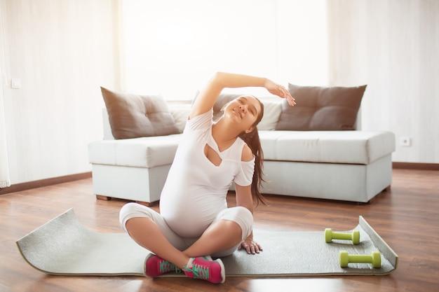 산전 운동. 임신 한 여자 집에서 운동