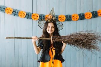 Pre-teen girl in Halloween costume holding broom