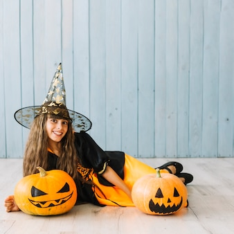 Pre-teen girl in witch costume lying on floor with pumpkins
