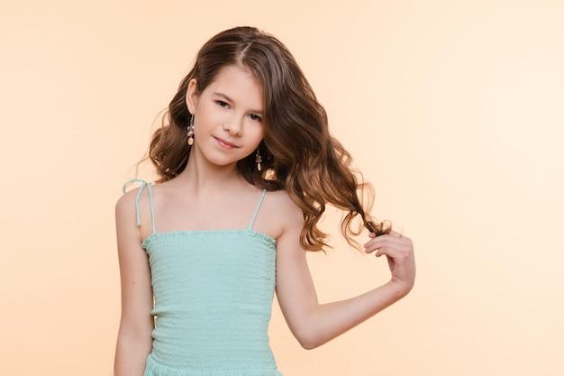 파란 드레스에 아름 다운 머리를 가진 사전 십 대 소녀.