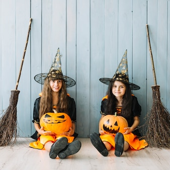 Pre-teen girls in witch costumes holding pumpkins and smiling