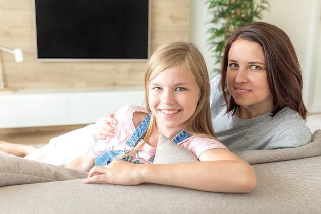 Мать и дочь pre teen, сидя на диване, улыбаясь, концепция счастливой семьи