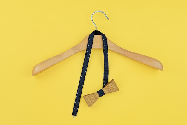 Pre-tied bow hanged into wooden hanger on yellow