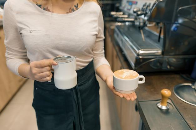 Крупный план молодого женского бариста держа молоко для pre