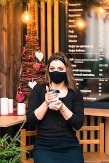 検疫終了後の公共の場での注意事項。カフェで医療マスクを持つ若い女性