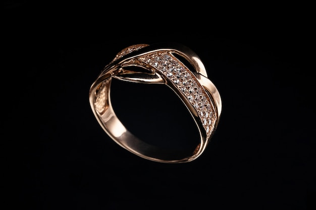 Precious gold ring with stones and reflection on glass