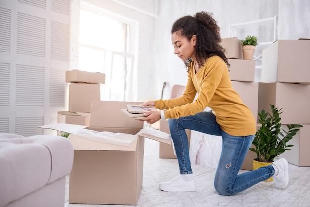 大事な思い出。引っ越す前に荷物をまとめながら、額入りの写真をいくつか箱に入れている魅力的な縮れ毛の女の子