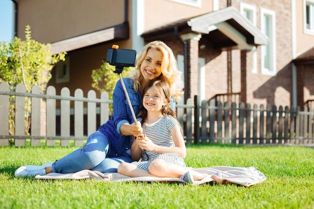 소중한 순간들. 그녀의 즐거운 어머니 옆에 깔개에 앉아 셀카 스틱을 사용하여 그녀와 함께 셀카를 찍는 사랑스러운 어린 소녀
