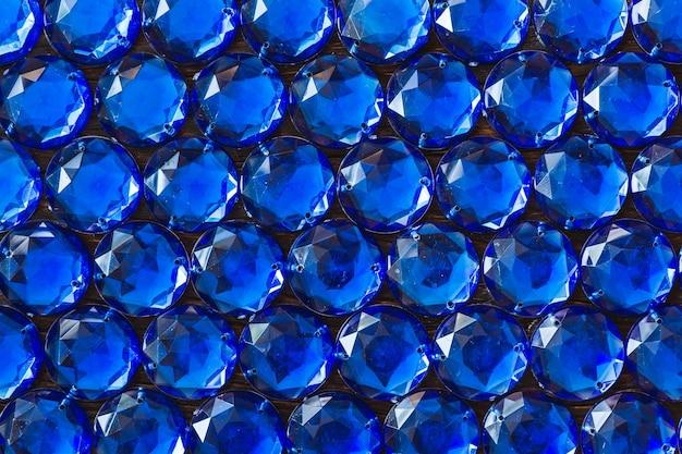暗い背景に貴重な輝くラインストーンの青い色