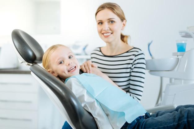 貴重なサポート。魅力的な少女と彼女の母親がカメラに向かってポーズをとっている間、少女は歯科医の椅子に座って彼女の母親