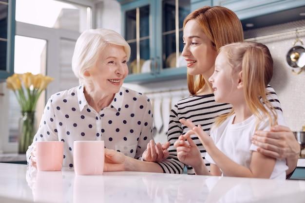 貴重な知恵。娘や孫娘と一緒にキッチンカウンターに座ってコーヒーを飲み、愛する女の子と経験を分かち合う魅力的な年配の女性