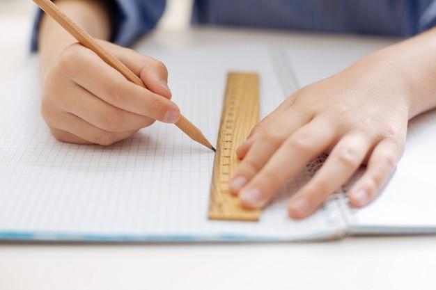 집에서 작업하는 동안 계획을 그리기 위해 연필과 통치자를 사용하는 정확하고 야심 찬 영리한 소녀