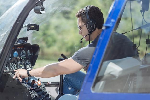정확한 데이터. 비행을 준비하는 동안 대시 보드에서 헬리콥터의 매개 변수를 확인하는 운동 젊은 남자