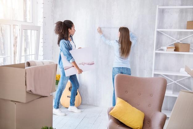 정확한 측정. 그들은 그들의 새 아파트를 장식하는 동안 벽과 사진을 들고 그녀의 룸메이트를 측정하는 아름 다운 어린 소녀