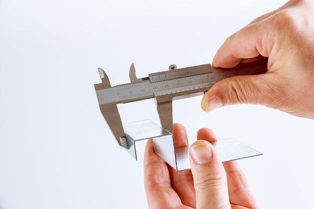 ノギスを使用した白い背景の金属部品の正確な測定