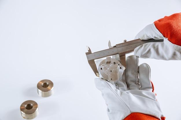 Точное измерение металлических деталей на белом фоне с помощью штангенциркуля.