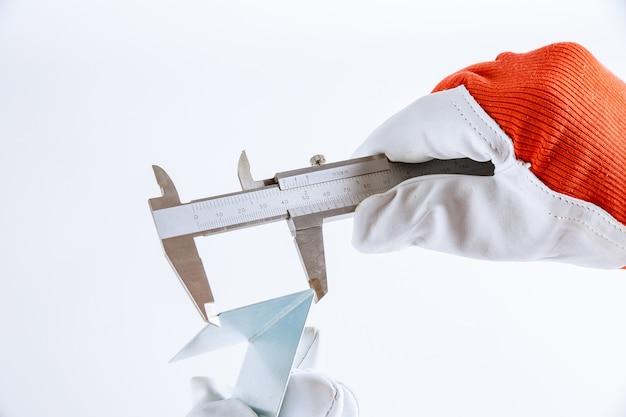 버니어 캘리퍼스를 사용하여 흰색 배경에 금속 부품의 정확한 측정