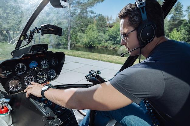 정확한 매개 변수. 헬리콥터의 조종사 부스에 앉아 비행을 준비하는 동안 대시 보드를 확인하는 잘 생긴 젊은 남자