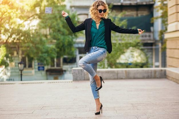 Preety donna elegante che cammina per strada in blue jeans che indossa giacca e camicetta verde, accessori moda, stile elegante, tendenze moda della primavera