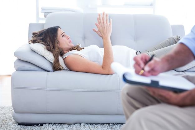Preganant женщина, расслабляющий на диване с терапевтом