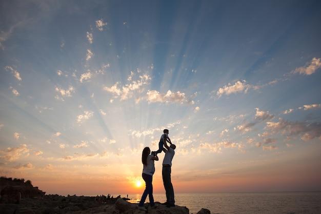 임신과 행복한 가족. 그녀의 남편과 아이가 바다 일몰을 걷고 손을 잡고 임신 한 아내