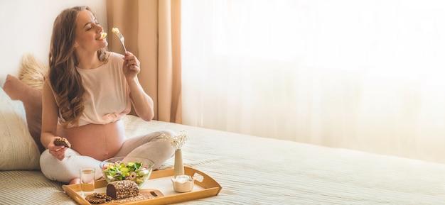 Беременность и здоровое органическое питание. беременная женщина, наслаждаясь салатом из свежих овощей в постели, свободное пространство