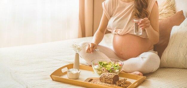 妊娠と健康的な有機栄養。妊娠中の女性がベッド、空き領域で新鮮野菜のサラダを楽しんで