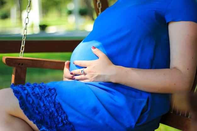 Беременность крупным планом девушки в голубом платье на скамейке