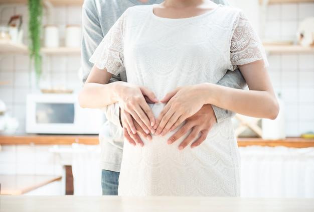 Концепция беременности - пара, делая форму сердца своими руками на беременный живот, беременная женщина и муж, держа руки в форме сердца на рему младенца жены.