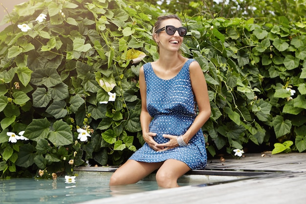 Pregnancy and maternity concept. attractive pregnant woman in trendy sunglasses relaxing at health resort, sitting outdoors at swimming pool with her legs underwater