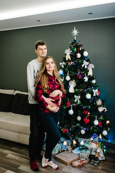 Концепция беременности, людей и ожидания - счастливая беременная женщина и мужчина возле елки в интерьере дома. ночное рождество. наслаждаемся семейным отдыхом. веселого рождества и счастливого нового года.
