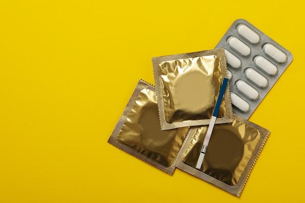 노란색 배경에 임신 테스트, 콘돔 및 알약
