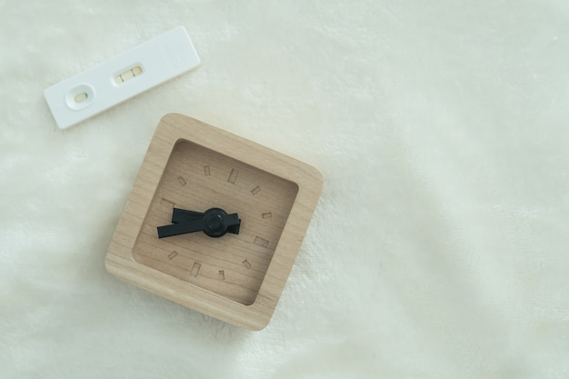 Pregnancy test with positive pregnant and wooden clock: time for baby planning