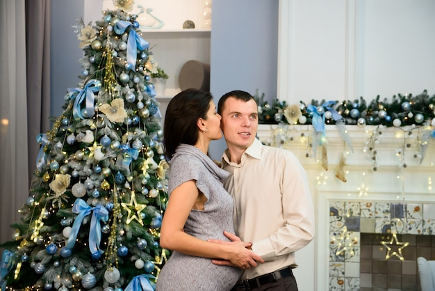 Pregnancy, winter holidays and people concept - happy pregnant wife with husband at home at christmas.