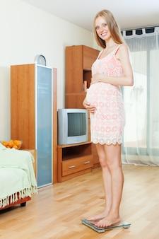 Pregnancy woman  on bathroom scale